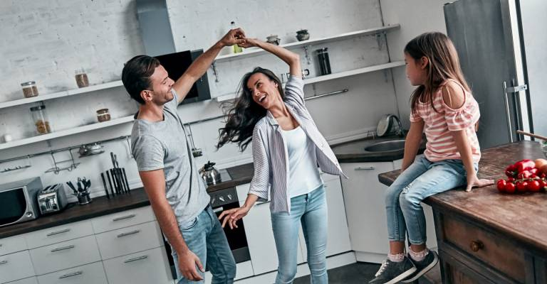 Dansend stel in keuken terwijl kind toekijkt zittend op aanrecht